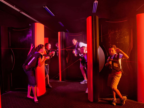 Family playing indoor laser tag in a black light room in Branson.