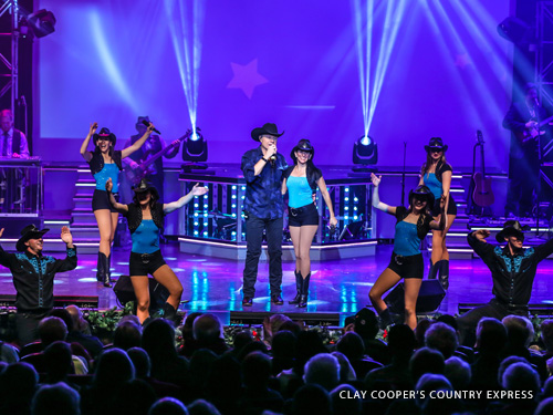 Country singer singing alongside cast of singers and dancers on a live show stage in Branson.