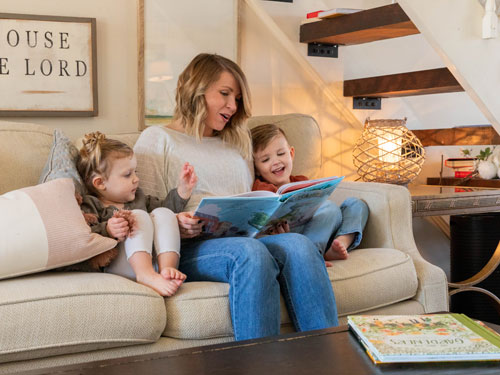 Mom reading her son and daughter a book from a living room in Branson.