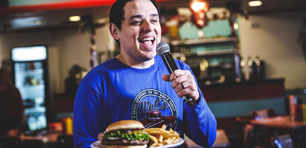 Singing server at a small diner in Branson singing while serving a burger and fries.
