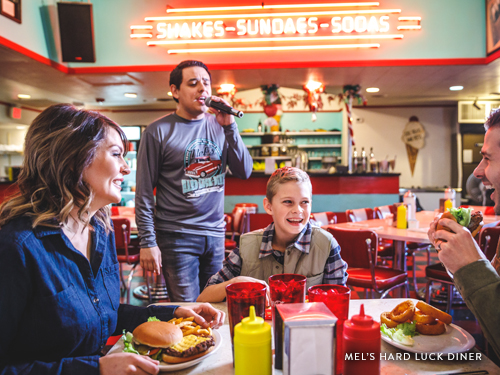 Family of three at a diner in Branson where you you are served by singing servers.