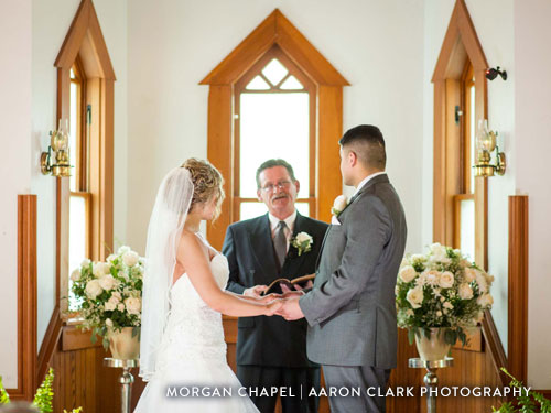 Indoor chapel wedding venue. Couple standing at alter taking their vows.