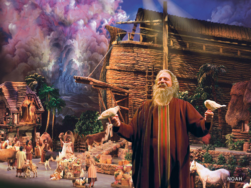 Man dressed up as a bible character is surrounded by birds and animals on a live show stage featuring an Ark in Branson.