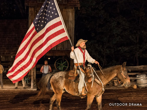 Man on horse holding a large American flag and performing in an outdoor drama in Branson.