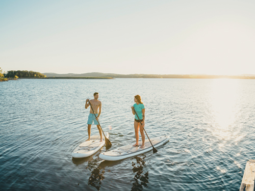 Man and woman paddleboarding on a lake in Branson.