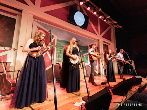 Petersen family of six playing their bluegrass instruments on stage.