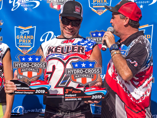 Man presenting trophy to winner of powerboat race in Branson.