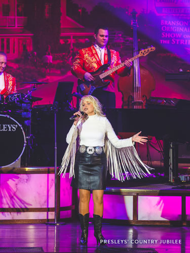Woman with curly blonde hair who is wearing a white fringe shirt and leather skirt while performing a classic country song on a live show stage in Branson.