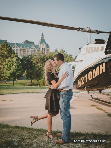 Recently engaged couple kissing in front of a helicopter.