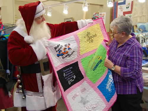 Santa showing a woman shopper a quilt in a quilt store.
