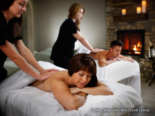 Husband and wife being given deep back massages at a spa in Branson.