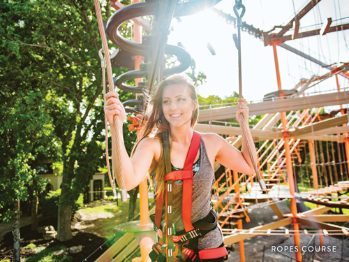 Woman climbing through outdoor ropes course in Branson.
