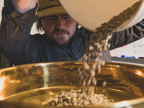 Man pouring coffee beans into a coffee roasting machine in Branson.