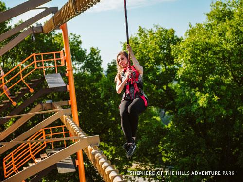 Woman climbing through outdoor ropes course in Branson.