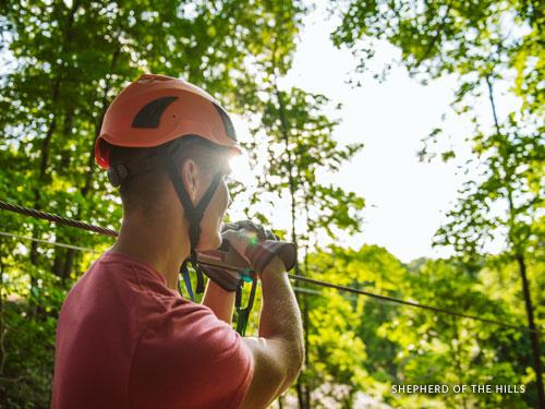 Man riding on outdoor zipline at an adventure park in Branson.