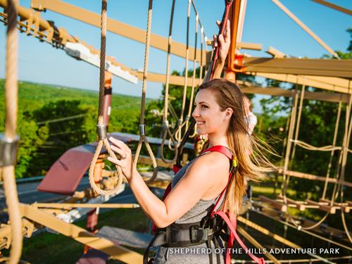 Girl climbing through an outdoor ropes course in Branson.