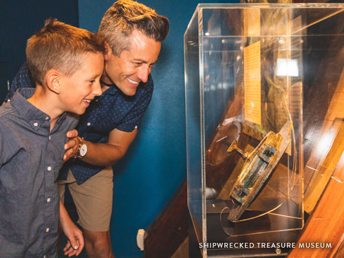 Father and son looking at an underwater treasure displayed in a museum in Branson.