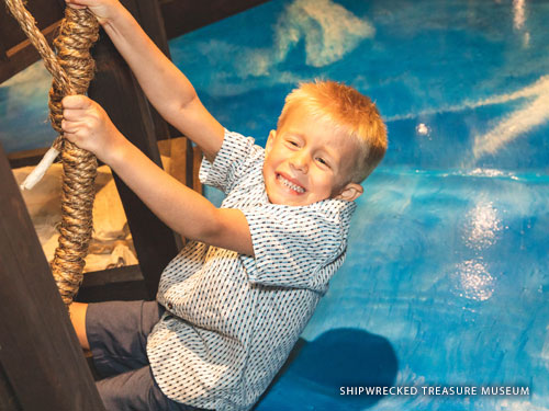Young boy pulling on two ropes inside an interactive museum in Branson.