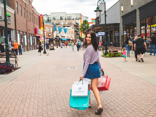 Young woman holding shopping bags and walking through outdoor shopping center in Branson.