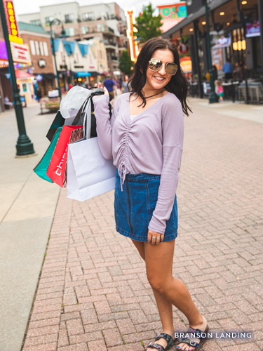 Girl holding shopping bags at an outdoor shopping mall.