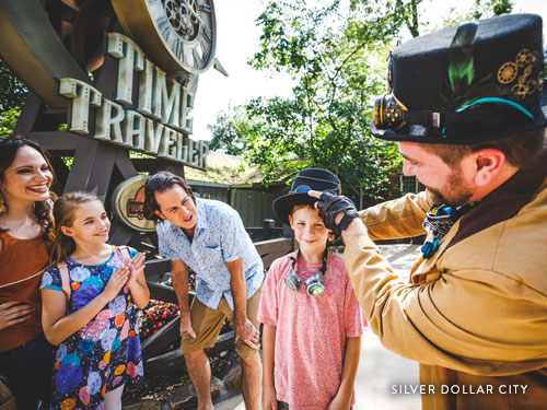 Family interacting with Silver Dollar City character at Time Traveler roller coaster.