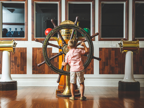 Young boy at a boat steering wheel at Titanic Museum Attraction in Branson.