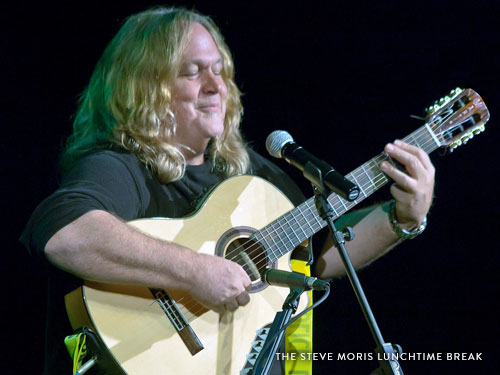 Man with long hair singing and playing guitar on live show stage in Branson.