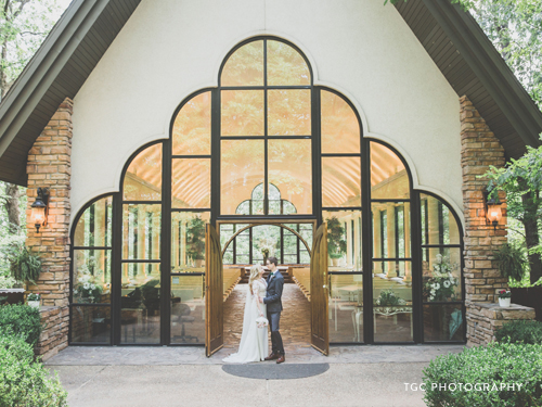 Recently married couple standing in front of a glass chapel in the Ozarks.