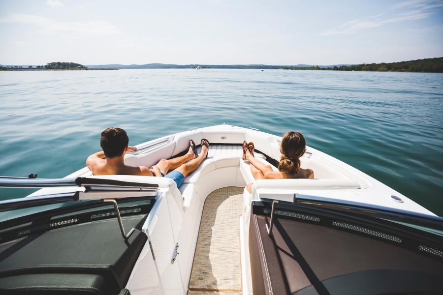 A man and a woman sit in the bow of a boat looking across the water on Table Rock Lake