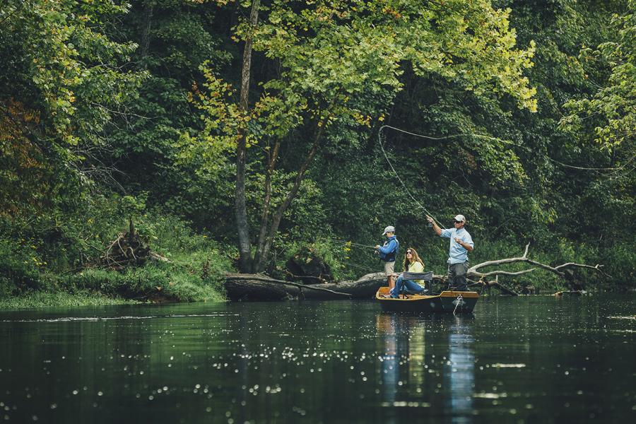 Father mother and son fly fish from a small boat in a lush wooded area on Lake Taneycomo