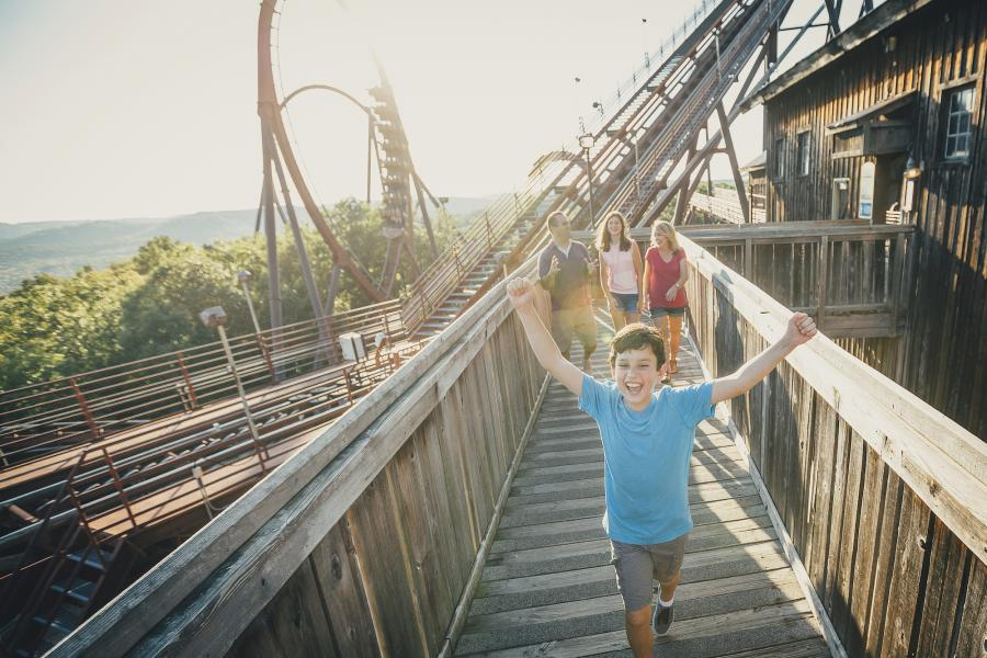 Kid running happily along with a roller coaster in the background.
