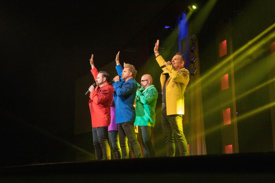 Members of the Branson live show SIX singing on stage.