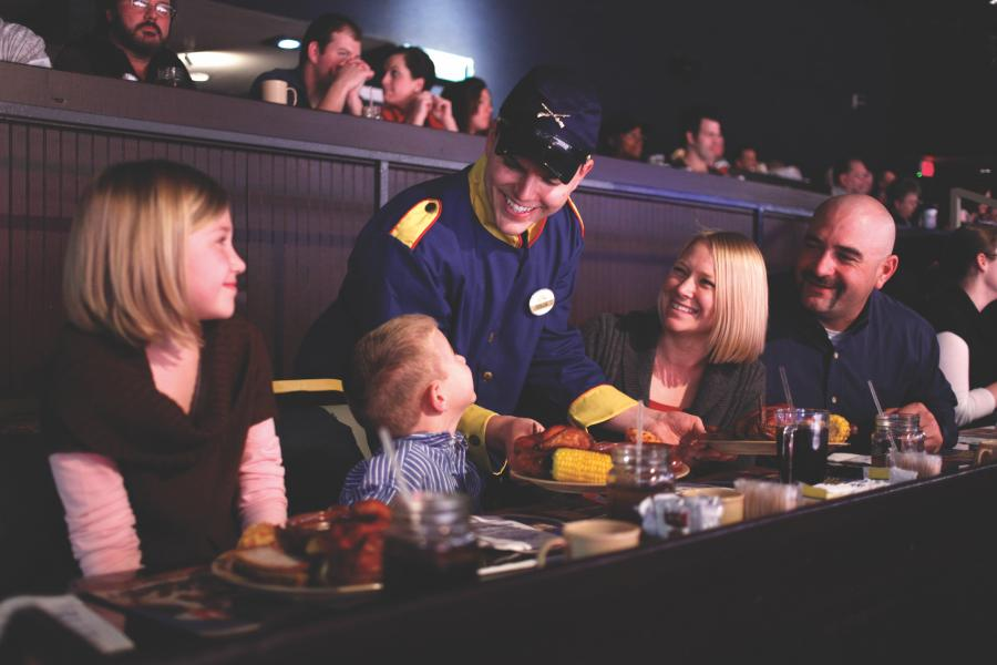 Family of four being served dinner by a waiter a Dolly Parton's Stampede Dinner Attraction in Branson.