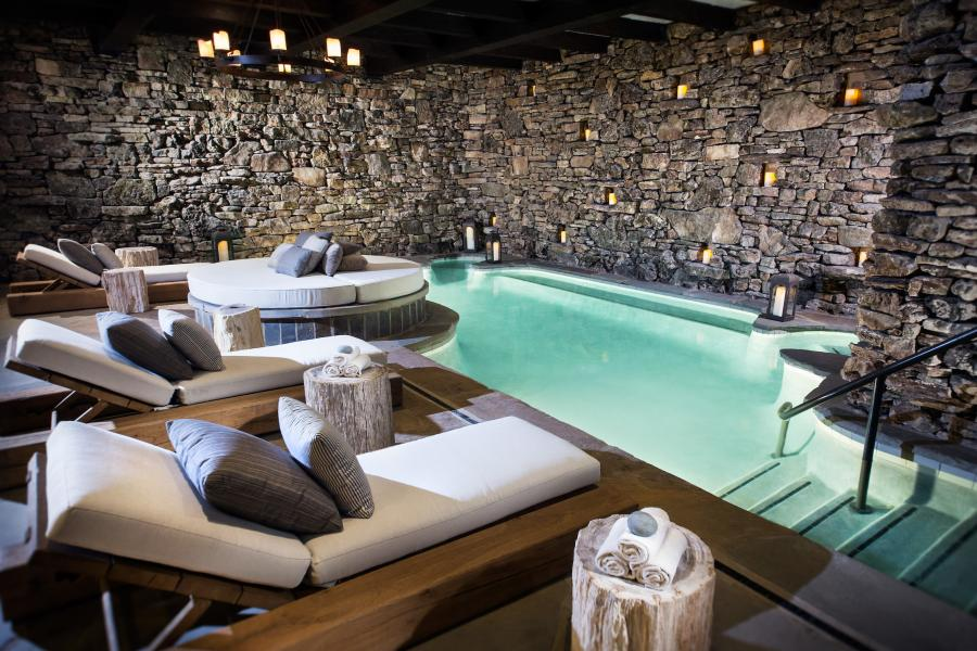 Relaxing spa with stone walls and a pool.
