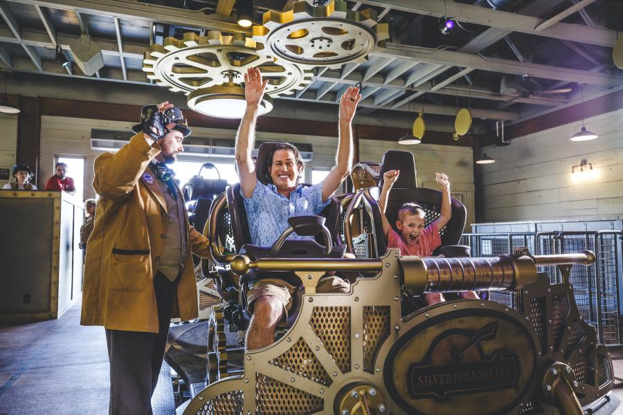 Father and son raising their arms in rollercoaster cart at the beginning of the ride.