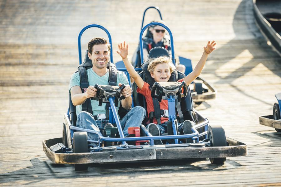 Father and son riding in a go kart with sons arms raised in the air.
