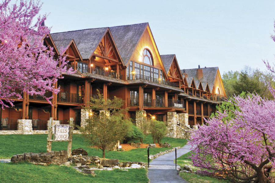 Exterior of Big Cedar Lodge with pink blossoms on trees.