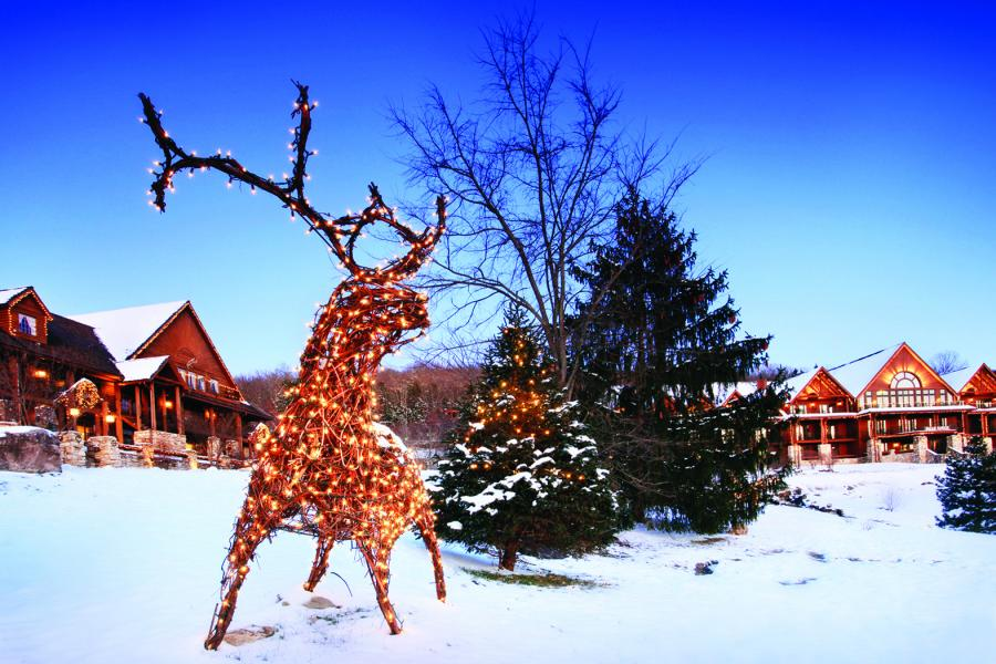 Reindeer made out of wood and string lights standing in front of Big Cedar Lodge cabins on snow-covered ground.