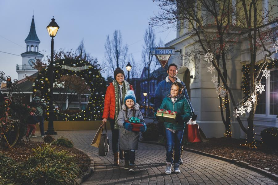 Family of four carrying shopping bags and Christmas gifts at Grand Village Shops in Branson, Missouri.