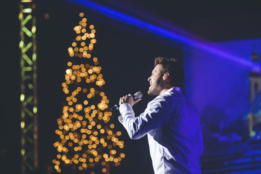 Singer from The Haygoods show singing into a microphone in front of a Christmas tree with lights.