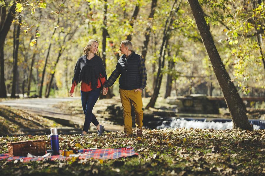 Man and woman holding hands and walking towards a picnic blanket laid out over leaves that have fallen from surrounding trees in Dogwood Canyon.