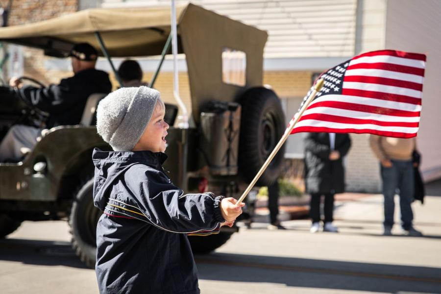 little boy waves flag in front of military jeep at veterans day parade in branson mo