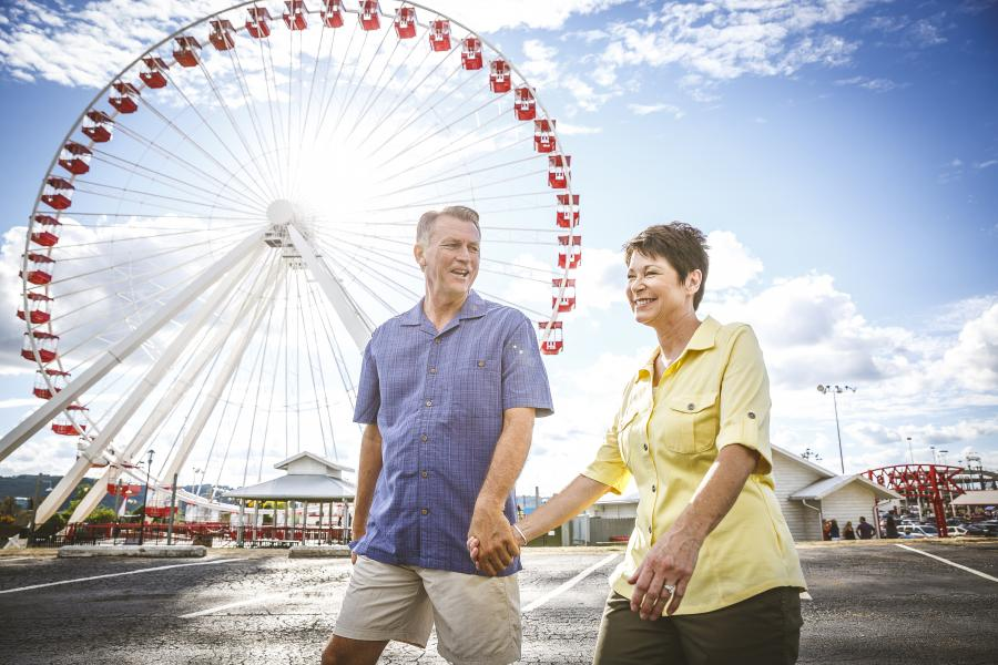 Couple holding hands walks in front of Branson Ferris Wheel.