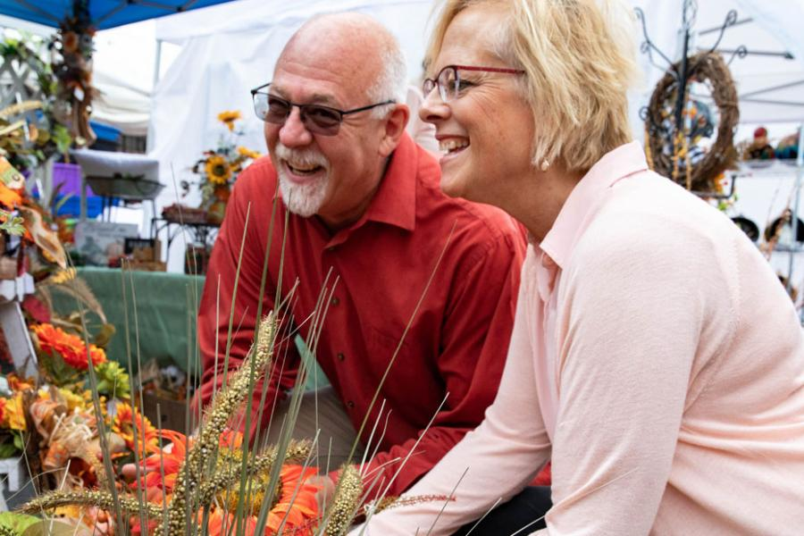 Husband and wife shopping at an outdoor fall craft fair in Branson.