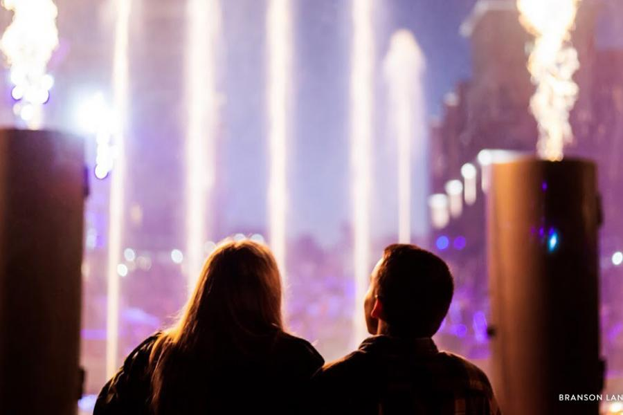 Couple standing in front of Branson Landing fire and fountain show in Branson.