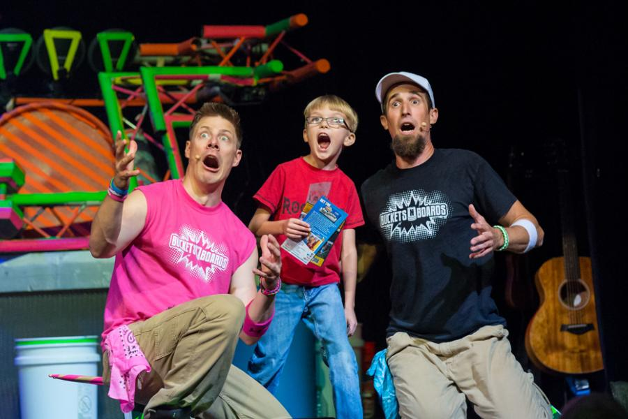 Two men and a young boy shocked by what they see in the audience at a live show in Branson.