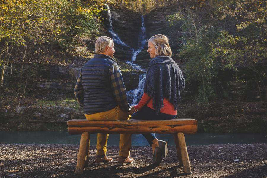Man and woman sitting on a wooden bench surrounded by a scenic view of nature in Branson.