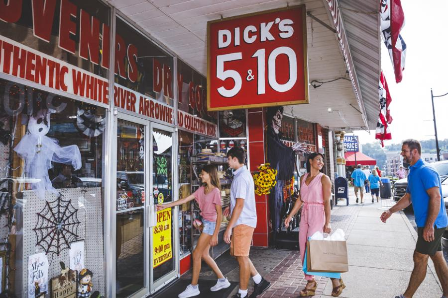 Family of four wearing cute summer clothes and walking into a historic nickle and dime store in downtown Branson.