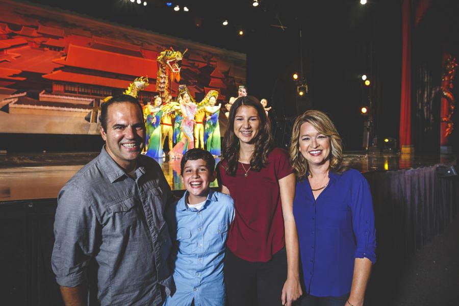 Family of four standing in front of a live show stage in Branson with Chinese acrobat performers on stage behind them.