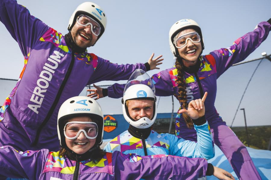 Family of three in purple suits about to fly with an instructor at an outdoor skydiving aerodium in Branson.